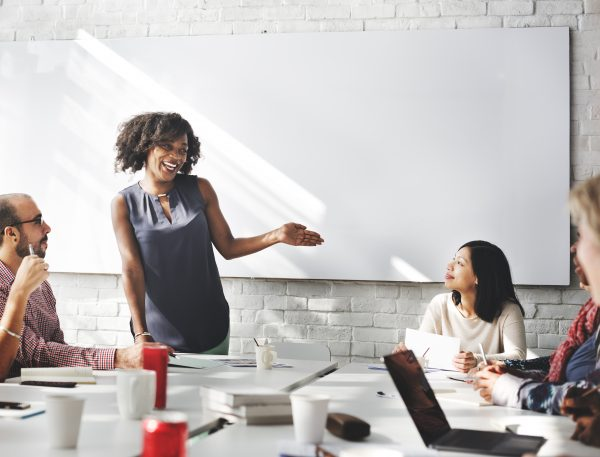 Image of a woman presenting to a group in a conference room